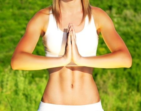 body posture: Peaceful yoga outdoor, healthy sporty female body over green natural background, body care and fitness concept