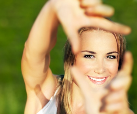 Jolie fille ayant extérieur fun, faire cadre avec les mains, la prise de photos avec l'appareil photo imaginaire, mise au point sélective