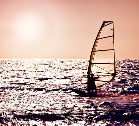 Windsurfer silhouette over sea sunset, beautiful beach landscape, summertime fun, sport, activities, vacation and travel concept photo