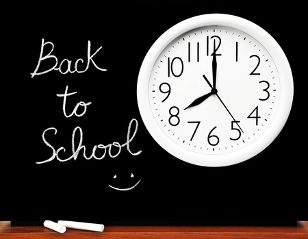 Back to school concept, handwriting on a black chalkboard with big white clock  Stock Photo - 10184111