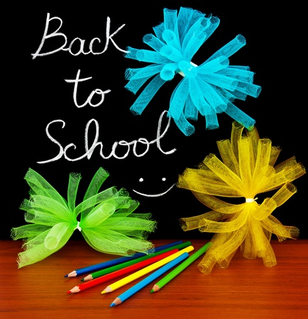 Back to school concept, handwriting on a black chalkboard with colorful objects photo