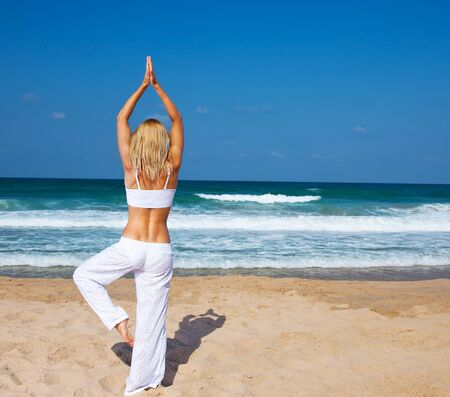 Healthy yoga exercise on the beach, slim sporty body training, leisure & meditation, vacation, sport, health care concept, over natural background photo