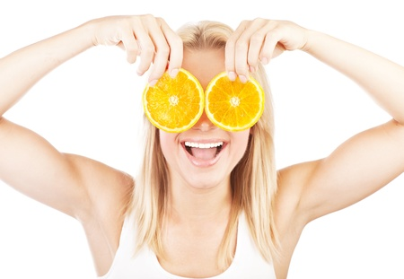 Funny girl portrait, holding oranges over eyes, conceptual image of healthy eating, dieting & skincare photo
