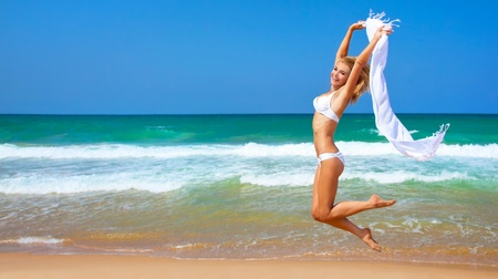 beach model: Jumping happy girl on the beach, fit sporty healthy sexy body in bikini, woman enjoys wind, freedom, vacation, summertime fun concept Stock Photo