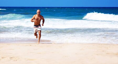 Healthy man running on the beach, doing sport outdoor, freedom, vacation, heath care concept with copy space over natural background photo