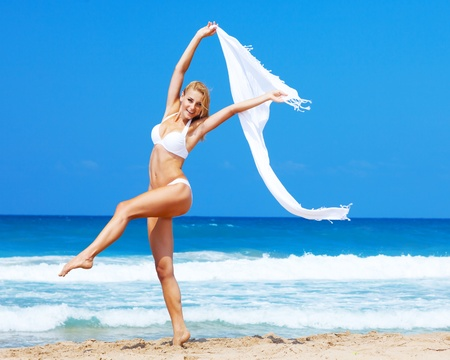 young woman legs up: Jumping & dancing happy girl on the beach, fit sporty healthy sexy body in bikini, woman enjoys wind, freedom, vacation, summertime fun concept Stock Photo