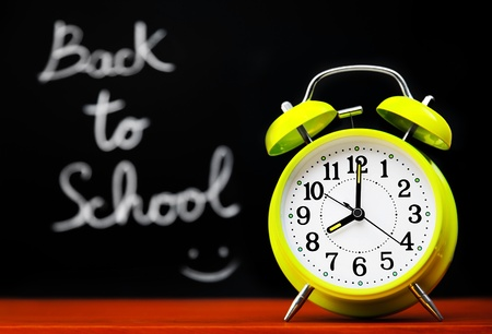 Back to school conceptual image with alarm clock & chalkboard in the classroom Stock Photo - 10325234