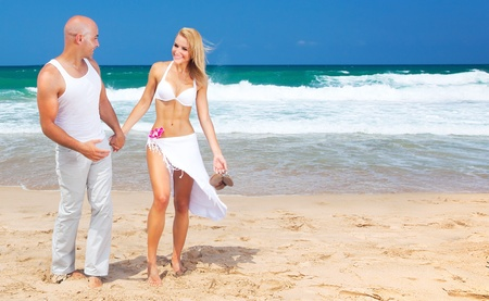Happy couple walking on the beach, young new family spends honeymoon at tropical resort, holding hands, handsome man & beautiful woman in love, vacation & travel concept Stock Photo - 10325228