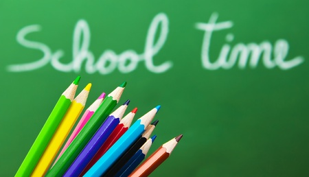 Back to school concept, green chalkboard with handwriting and set of colorful drawing pencils  photo