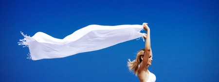 Female enjoying wind, portrait over blue sky, raised arms, natural background, freedom concept photo