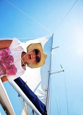 Happy female tourist, having fun on sailboat, summertime sailing vacation, outdoors photo