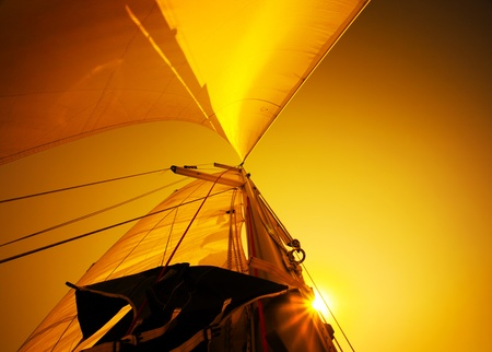 Sail over warm yellow sunset sky, sailboat over natural background photo