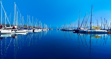 Yacht port over blue nature scene, row of luxury sailboats reflected in water  스톡 콘텐츠