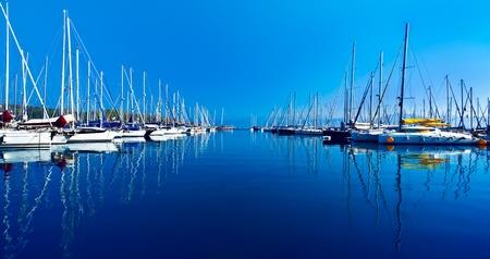Yacht-poort over blauwe natuur scene, rij van luxe zeilboten weerspiegeld in het water Stockfoto