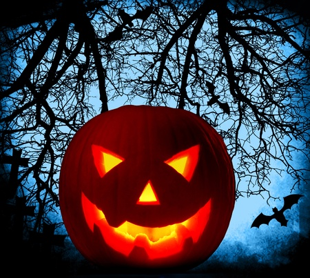 Halloween pumpkin background with glowing jack-o-lantern at night, cemetery in the dark forest  photo