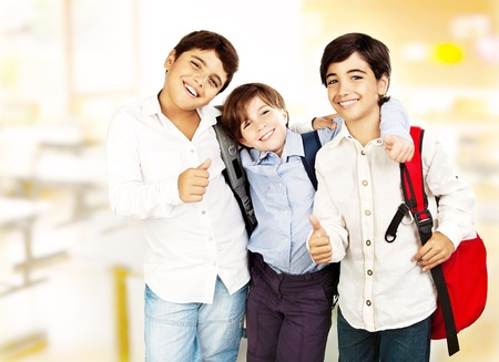 best schools: Happy schoolboys with thumbs up, back to school, boys best friends and classmates hugging, smiling, at the classroom, teenage education concept Stock Photo