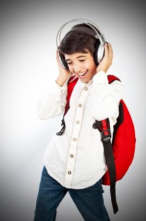 listening to music: Chico bastante adolescente disfrutando de m�sica, sosteniendo la cabeza con auriculares, expresar placer y diversi�n, cantando una canci�n Foto de archivo