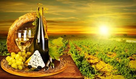 Wijn en kaas romantisch diner buiten, tafel voor twee met wijngaard uitzicht, verse druiven en wijnglas in het restaurant, warme herfst zonsondergang, druif veld landschap bij de oogst, voedsel stilleven