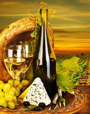 Wine and cheese romantic dinner outdoor, table for two with vineyard view, fresh grapes and wineglass at restaurant, warm autumn sunset, grape field landscape at harvest, food still life photo