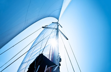 yachting: Sail over clear blue sky, sailboat over natural background with sunlight, summertime activities and extreme sport Stock Photo