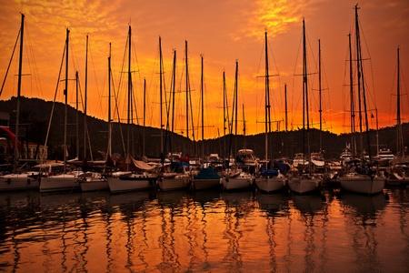 Porto turistico sul tramonto arancione con fila di barche a vela di lusso