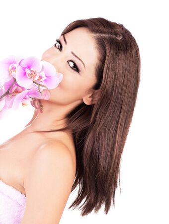 Beautiful young female portrait, smelling purple orchid, isolated on white background with white text space, beauty and spa concept photo
