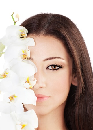 modeling: Closeup on beautiful face with white orchid flower, perfect clean skin, young female portrait,  isolated on white background with white text space, beauty and spa concept
