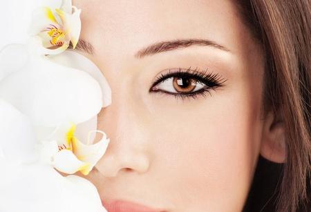 Gros plan sur le beau visage avec orchidée blanche fleur, parfaite peau propre, le jeune portrait de femme, la beauté et la notion de spa