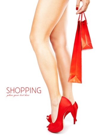 legs heels: Beautiful female legs with red high heels holding shopping bags isolated on white background, money spending concept