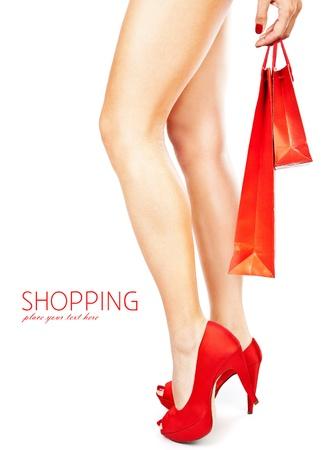 tacones rojos: Hermosas piernas femeninas con tacones rojos sosteniendo bolsas aisladas sobre fondo blanco, concepto de gasto de dinero Foto de archivo