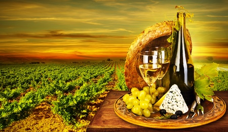 grape field: Wine and cheese romantic dinner outdoor, table for two with vineyard view, fresh grapes and wineglass at restaurant, warm autumn sunset, grape field landscape at harvest, food still life
