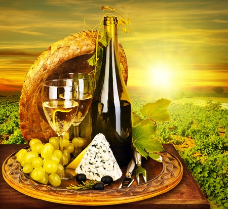 food and drink industry: Wine and cheese romantic dinner outdoor, table for two with vineyard view, fresh grapes and wineglass at restaurant, warm autumn sunset, grape field landscape at harvest, food still life
