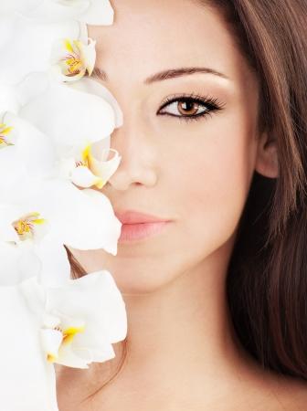 gezicht: Close-up op mooie gezicht met witte orchideebloem, perfect schone huid, jonge vrouwelijke portret, schoonheid en wellness concept