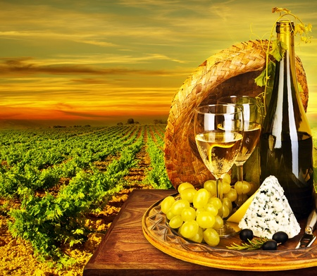 Wine and cheese romantic dinner outdoor, table for two with vineyard view, fresh grapes and wineglass at restaurant, warm autumn sunset, grape field landscape at harvest, food still life