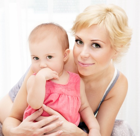 blonde mom: Portrait of a happy young mother holding baby girl, cute family at home, loving mom