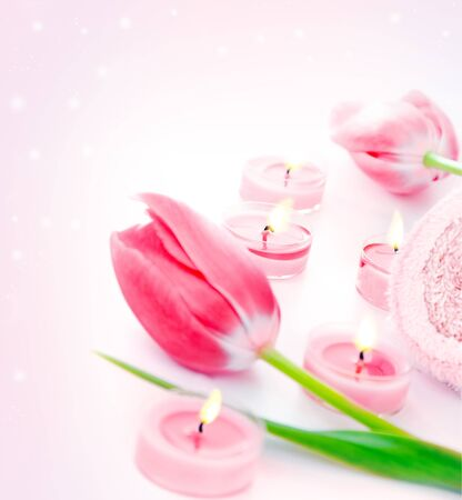 Spa candle with pink tulip flowers, aromatherapy day spa salon, relaxation and beauty treatment concept, objects over pink glitter shiny background  photo