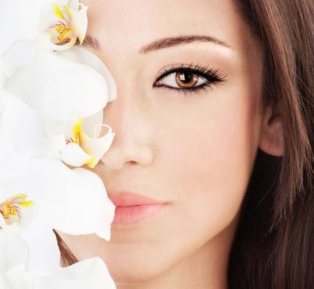 白い蘭の花の美しい顔にクローズ アップ完全なきれいな肌、若い女性の肖像画の美しさとスパのコンセプト