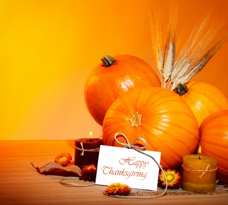 Thanksgiving holiday, pumpkin border still life decoration with candles and wheat over yellow studio light background, greeting card with text space, harvest concept photo