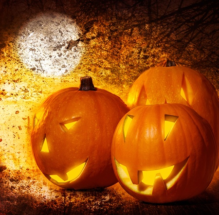 Grunge Halloween background, pumpkins on the cemetery at night, scary spooky decoration, autumn holiday photo