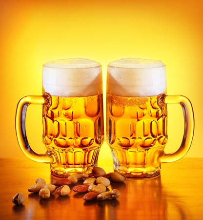 Glass of cold beer drink and nuts isolated on yellow warm background, festival of beer, oktoberfest autumn holiday photo
