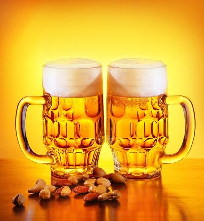 comida alemana: Vaso de bebida de cerveza fr�a y nueces aislados en fondo c�lido amarillo, festival de la cerveza, oktoberfest, fiesta de oto�o