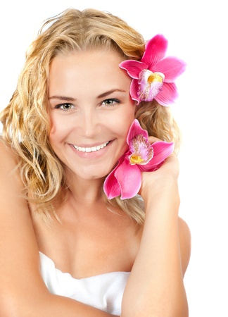 Beautiful girl with pink flowers, happy female smiling and holding orchids, isolated on white background, pretty young woman portrait, spa and relaxation concept photo