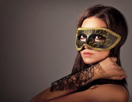 sexy costume: Beautiful female wearing mask, mysterious girl at masquerade,stylish woman portrait studio shot Stock Photo