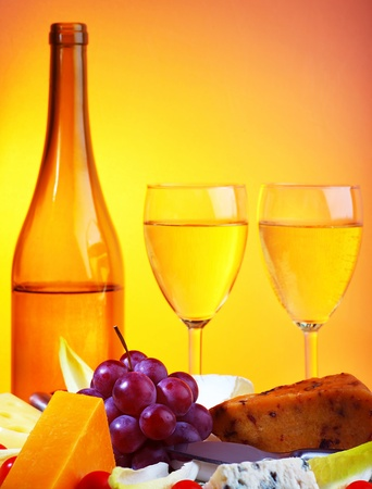 Romantic dinner, wine and cheese table setting, celebrating holidays, food still life over warm yellow studio light photo