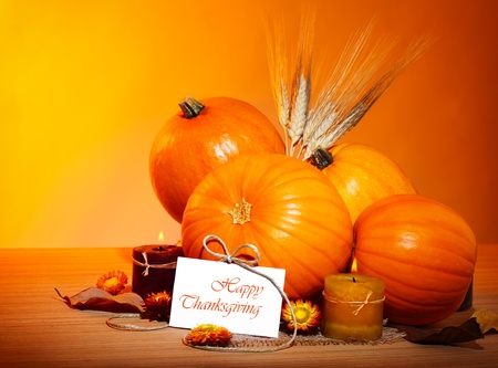 Thanksgiving holiday, pumpkin still life decoration with candles and wheat over yellow studio light background, greeting card with text space, harvest concept photo