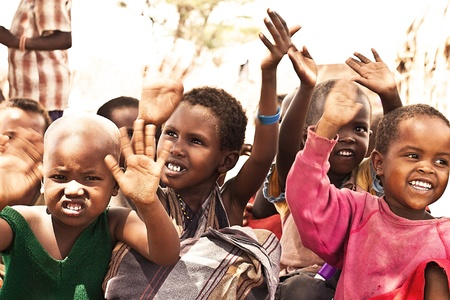 SAMBURU, KENYA - NOVEMBER 8: portrait of African group of kids with hands up on November 8, 2008 in tribal village near Samburu National Park Reserve, Kenya. Stock Photo - 10820490