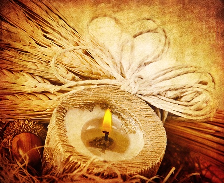 Warm candle light, decoration with wheat, dark grunge autumn background, thanksgiving holiday ornament photo