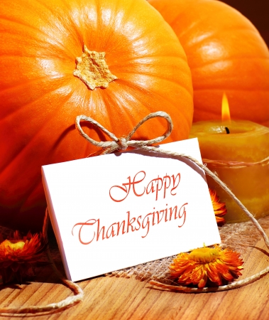 thanksgiving greeting: Thanksgiving holiday, pumpkin still life decoration with candle on the wooden table, greeting card with text space, harvest concept