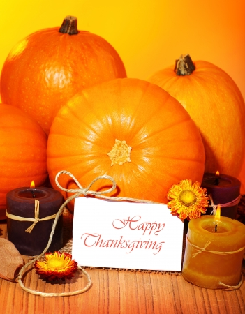 Thanksgiving holiday, pumpkin still life decoration with candle on the wooden table, greeting card with text space, harvest concept photo