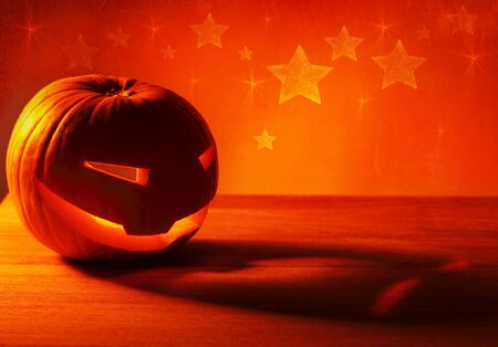 Halloween pumpkin glowing candle, warm autumn holiday background, traditional jack-o-lantern, night party decoration photo